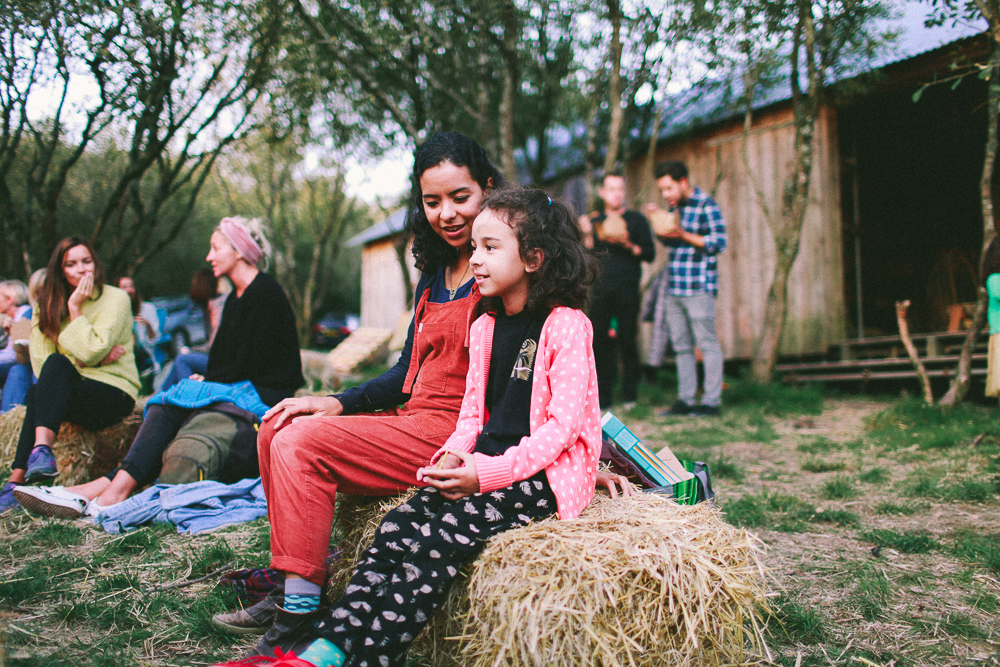 Adele and her daughter sit on a hay bale at the Stranger Firelight at Kudhva