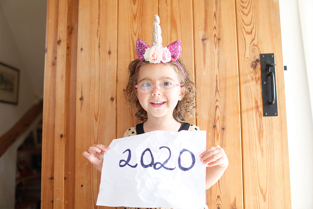 "Four year old in glasses holds a sign saying ""2020"" while she wears a unicorn headband"